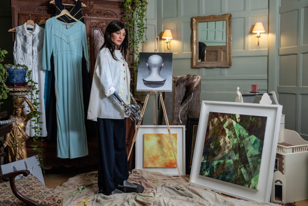 Ai-DA with Her Paintings (Photographer Victor Frankowski)